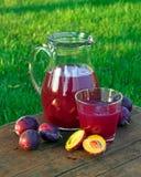 Подрежьте сок в стекле и carafe с сливами Стоковые Фото