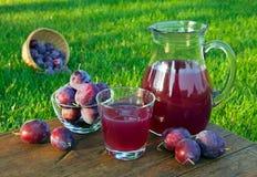Подрежьте сок в carafe и стекло с сливами Стоковые Фото