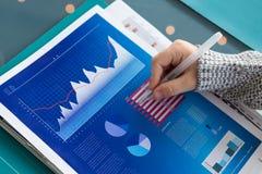 Подрезанная рука бизнесмена анализируя данные в офисе Стоковые Фотографии RF