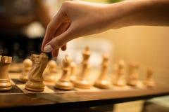 Подрезанная рука коммерсантки играя шахмат Стоковые Фотографии RF