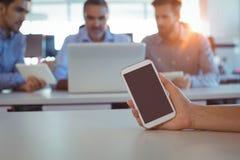 Подрезанная рука персоны дела держа мобильный телефон на столе Стоковые Фотографии RF