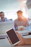 Подрезанная рука персоны дела держа smartphone на столе Стоковая Фотография