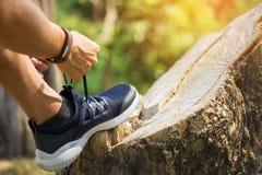 Подрезанная съемка бегуна молодого человека затягивая шнурки ботинка хода, Стоковое фото RF