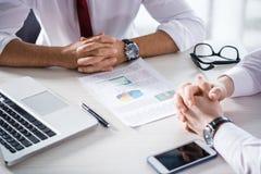 Подрезанная съемка бизнесменов сидя на таблице с диаграммами, компьтер-книжкой и smartphone Стоковые Изображения RF