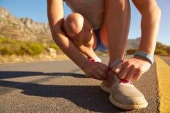 Подрезанная съемка женского jogger делая вверх по ее шнурку ботинка Стоковые Изображения RF