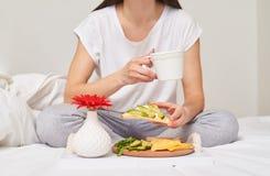 Подрезанная съемка женщины в выпивая чае и сандвиче еды Стоковое Изображение