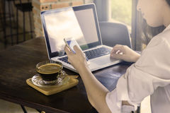Подрезанная съемка женщины на кафе работая на ее портативном компьютере и Стоковые Изображения RF