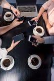 Подрезанная съемка команды дела на встрече с smartphones в кафе Стоковые Фото