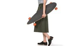 Подрезанная съемка стильной девушки битника в юбке держа скейтборд Стоковое Изображение