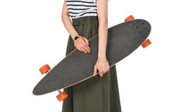 Подрезанная съемка стильной девушки битника в юбке держа скейтборд Стоковое Фото