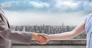 Подрезанное изображение бизнесмена и коммерсантки тряся руки против города Стоковая Фотография RF