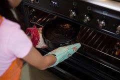 Подрезанное изображение девушки держа контейнер с тортом в печи Стоковые Изображения