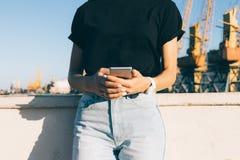 Подрезанное изображение девушки держа телефон в городе в summe Стоковые Изображения RF