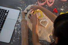 Подрезанное изображение девушки делая форму на тесте в кухне Стоковая Фотография