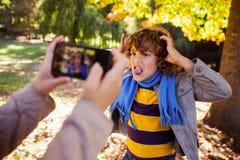 Подрезанное изображение девушки фотографируя мальчика делая сторону в парке Стоковые Фотографии RF