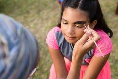 Подрезанное изображение женщины делая краску стороны на девушке Стоковые Изображения RF