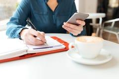 Подрезанное изображение женщины на таблице кафа Стоковое Фото