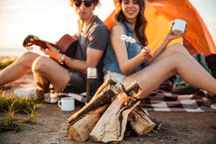 Подрезанное изображение пар в влюбленности жаря зефир пока располагающся лагерем Стоковое фото RF