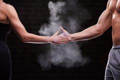 Подрезанное изображение рук человека и женщины спортсмена мышечных против темной предпосылки Стоковое фото RF
