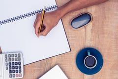 Подрезанное изображение сочинительства бизнесмена на тетради кофе на столе Стоковые Изображения