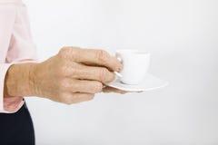 Подрезанное изображение старшей коммерсантки с чашкой эспрессо на офисе Стоковое Фото