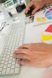 Подрезанные руки бизнесмена используя компьютер на столе в офисе Стоковые Изображения