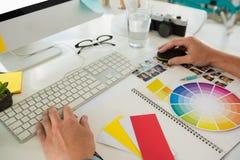 Подрезанные руки бизнесмена используя компьютер на столе Стоковое Изображение