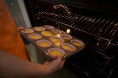 Подрезанные руки девушки держа олово булочки в печи Стоковая Фотография
