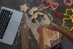 Подрезанные руки девушки делая форму на тесте на счетчике кухни Стоковые Фотографии RF
