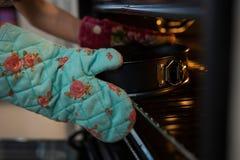 Подрезанные руки перчатки девушки нося держа контейнер с тортом в печи Стоковые Фото