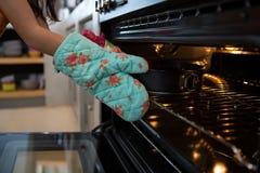 Подрезанные руки перчатки девушки нося кладя контейнер с тортом в печь Стоковая Фотография