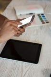 Подрезанные руки человека используя телефон на столе в офисе Стоковые Изображения RF