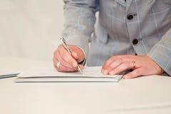 Подрезанный взгляд бизнесмена подписывая контракт Рука человека с концом ручки вверх Стоковое Изображение