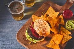 Подрезанный взгляд бургера, обломоков и пива на таблице Стоковые Фотографии RF