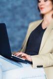 Подрезанный взгляд съемки молодой женщины работая на компьтер-книжке лежа на ее коленях Стоковая Фотография