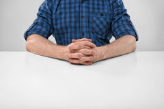 Подрезанный портрет человека сидя с его сжимал руки Стоковое Фото