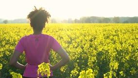 подростка девушки смешанной гонки бегун молодой женщины Афро-американского женский отдыхая после jogging в поле желтых цветков видеоматериал