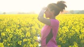 подростка девушки смешанной гонки бегун молодой женщины Афро-американского женский отдыхая после jogging в поле желтых цветков сток-видео