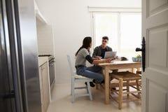 2 подростка используя портативный компьютер говоря на кухонном столе Стоковое фото RF
