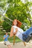 2 подростка на спортивной площадке качания в парке Стоковое Фото
