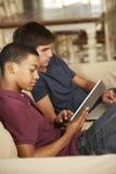 2 подростка сидя на софе дома используя планшет и компьтер-книжку Стоковая Фотография