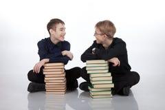 2 подростка с кучами книг Стоковые Фото