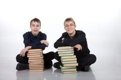2 подростка с стогами книг Стоковое фото RF
