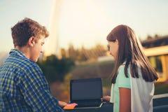 Подростки девушка и мальчик используя компьтер-книжку внешнюю Стоковые Фото