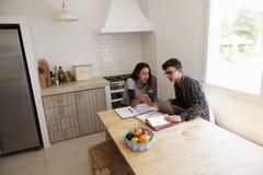 Подростки изучают с компьтер-книжкой и телефоном в кухне, повышенном взгляде Стоковое Изображение RF