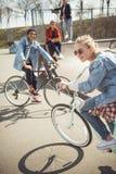Подростки имея потеху и ехать велосипеды в скейтборде паркуют Стоковое Фото