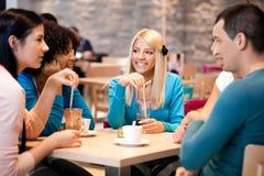 Подростки наслаждаются в кофе стоковые фото