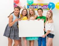 Подростки на вечеринке по случаю дня рождения держа знамя Стоковое Фото