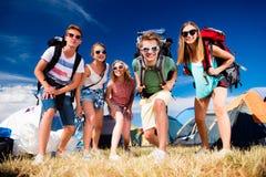 Подростки перед шатрами с рюкзаками, фестивалем лета Стоковые Фотографии RF