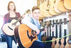 Подростки рассматривая гитары в магазине Стоковые Фотографии RF